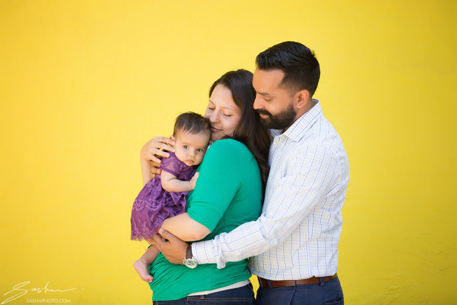 parents and infant yellow background