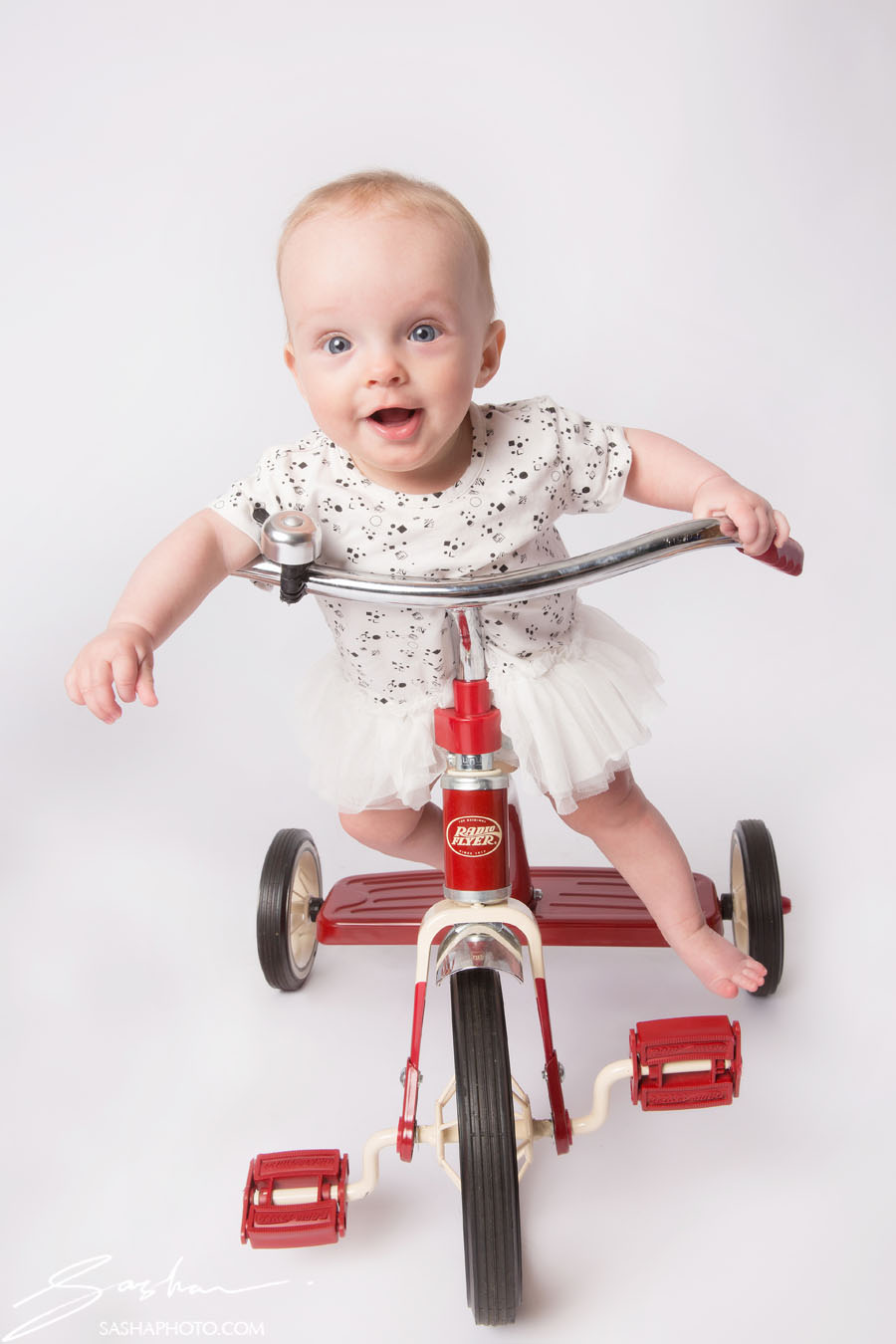 baby on red tricycle
