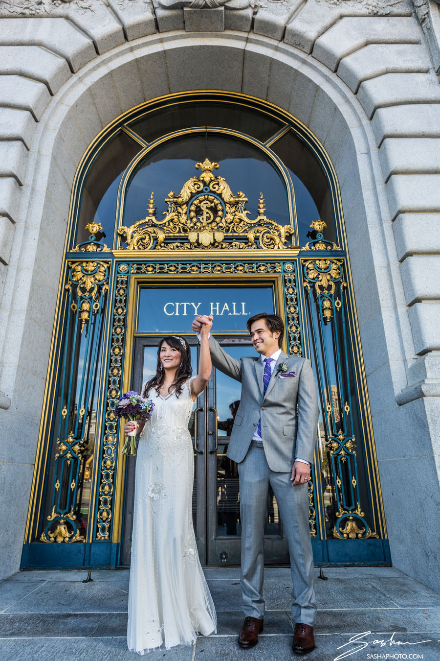 bride and groom outside city hall doors