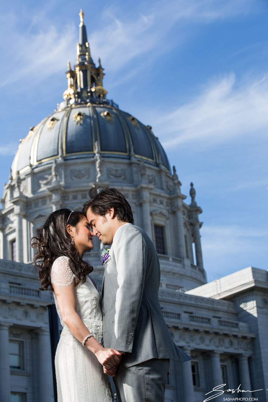 bride and groom with city hall dome in the background